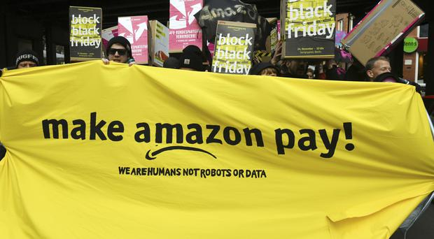 Demonstrators hold a banner and posters during a rally against the online retailer Amazon in Berlin (AP)