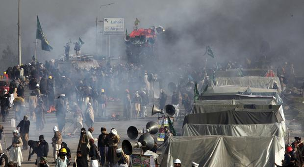 Demonstrators protest as police fire tear gas shells to disperse them (AP/Anjum Naveed)