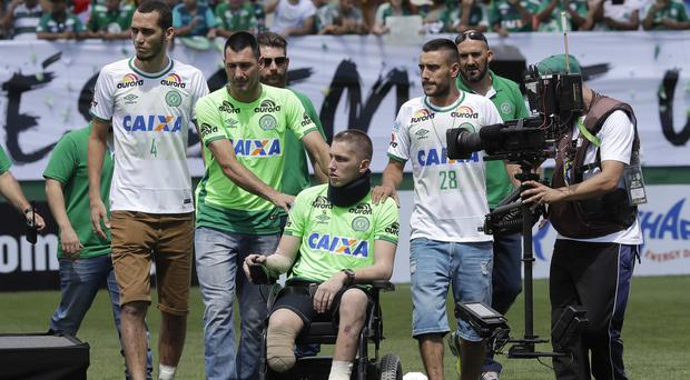 Chapecoense players Neto, left, goalkeeper Follmann, sitting in wheelchair, and Alan Ruschel, right, were the three players that survived a LaMia air crash,(AP Photo/Andre Penner, File)