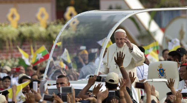 Pope Francis waves from pope-mobile as Burmese Catholics wave flags ahead of a Mass on Wednesday, in Yangon, Burma. (AP Photo/Gemunu Amarasinghe)