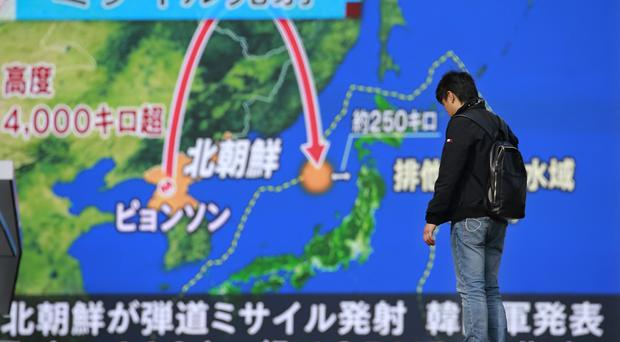 A man stands in front of a huge screen showing TV news program reporting North Korea's missile launch, in Tokyo, Wednesday, November 29, 2017. (AP Photo/Shizuo Kambayashi)