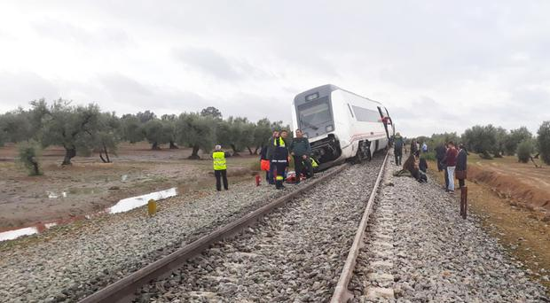Passengers and emergency workers stand by a coach of a train that derailed after part of a track became flooded near the town of Arahal, southern Spain (Emergencias 112 Andalucia via AP/PA)