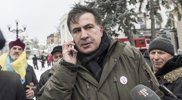 Former Georgian president Mikheil Saakashvili is surrounded by his supporters as they camp out outside parliament in Kiev demanding the resignation of Ukraine's president (AP Photo/Evgeniy Maloletka)