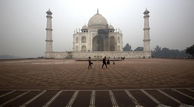 Tourists walk around the Taj Mahal as workers clean the monument in Agra, India (Manish Swarup/AP)