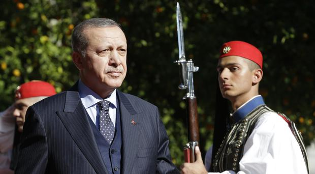 Turkey's President Recep Tayyip Erdogan reviews the Presidential Guard during a welcoming ceremony in Athens (Thanassis Stavrakis/AP)