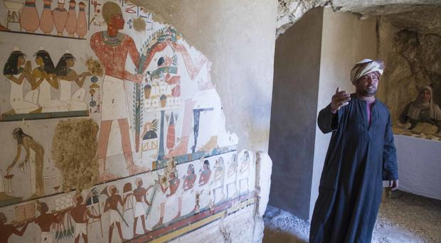 An Egyptian guard stands next to a funeral mural inside a newly discovered tomb on Luxor's west bank (Hamada Elrasam/AP)