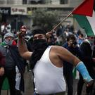 A protester throws a stone as others hold Palestinian flags during a demonstration in front of the US embassy in Aukar, east of Beirut, Lebanon (AP/Bilal Hussein)