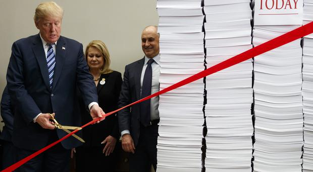 Trump, quite literally, cuts the red tape on regulations