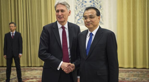 China's premier Li Keqiang, right, meets Chancellor Philip Hammond at the Great Hall of the People in Beijing (Fred Dufour/Pool Photo via AP)