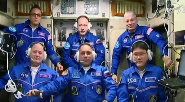 Scott Tingle, Anton Shkaplerov and Norishige Kanai, in the front row, join the crew (Nasa/AP)