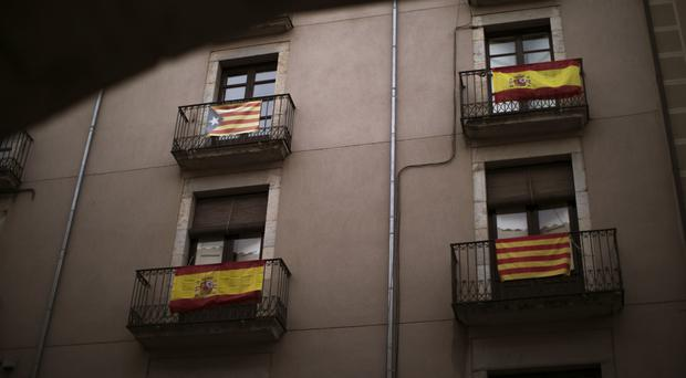 Balconies are seen decorated with Spanish, independence and Catalan flags in Girona as voters prepare to return to the polls (AP)