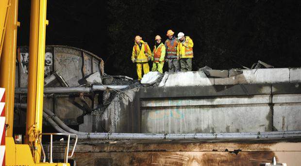 Workers examine a damaged bridge section at the site of the derailment of an Amtrak train in Dupont, Washington (AP)