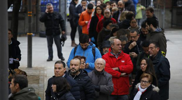 Voters line up outside a polling station to cast their ballot in the Catalan regional election (AP)