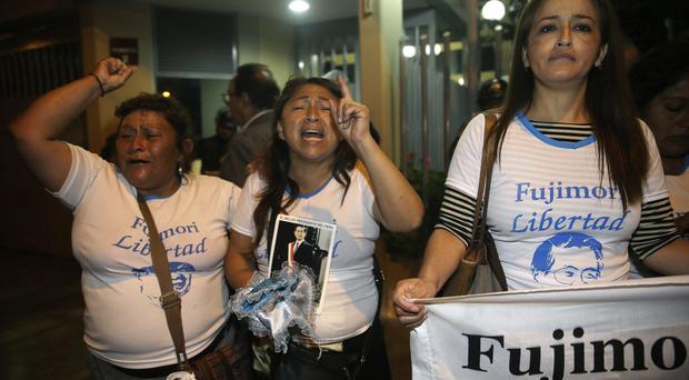 Supporters of former president Alberto Fujimori celebrate his medical pardon outside the clinic where the jailed leader was admitted (AP Photo/Martin Mejia)