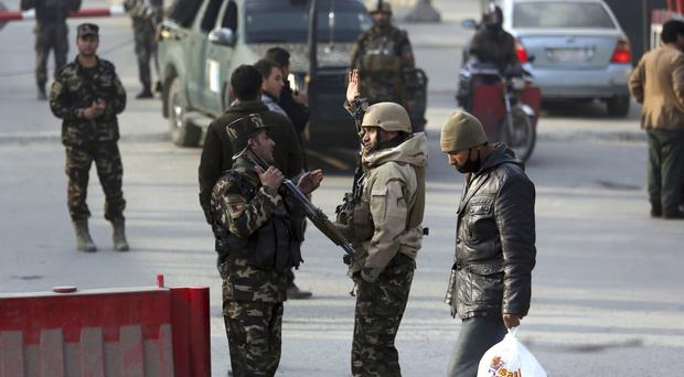 Afghan security personnel stand near the site of a suicide attack in Kabul, Afghanistan (AP)
