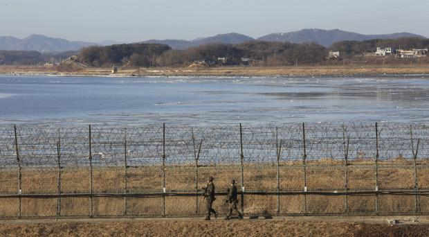 South Korean army soldiers patrol along the barbed-wire fence in Paju, South Korea, near the border with North Korea (AP)