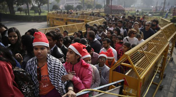 Hundreds of Indians wait in a queue to pray at the Sacred Heart Cathedral on Christmas Day, in New Delhi (AP/Altaf Qadri)