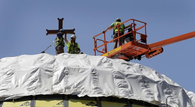 Construction workers adjust a temporary cross on the St Nicholas National Shrine in New York. (AP Photo/Mark Lennihan, File)