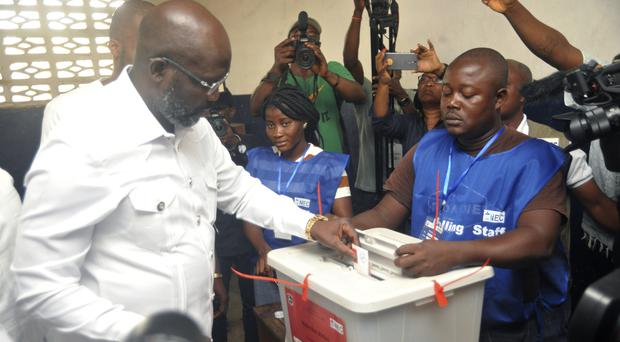 Former footballer George Weah casts his vote (AP)