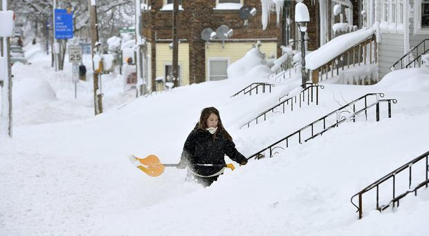 Rochelle Carlotti, 28, digs snow near her home in Erie (Greg Wohlford/Erie Times-News via AP)