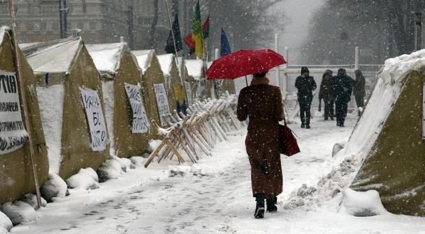 Under heavy snowfall a woman passes by a tent camp in front of the parliament building in Kiev, Ukraine (Efrem Lukatsky/AP)