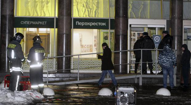 Police stand at the entrance of the supermarket after the explosion in St Petersburg (AP)