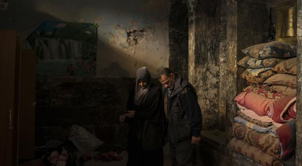Yahya Ali and Haifa Shehab look through the rubble in their house in the Old City of Mosul, Iraq