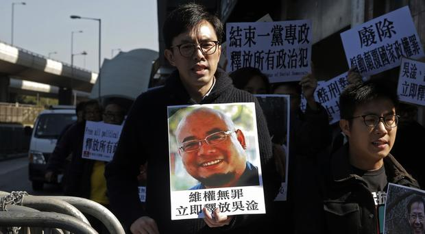 Pro-democracy activists hold pictures of Chinese activist Wu Gan in Hong Kong (Kin Cheung/AP)