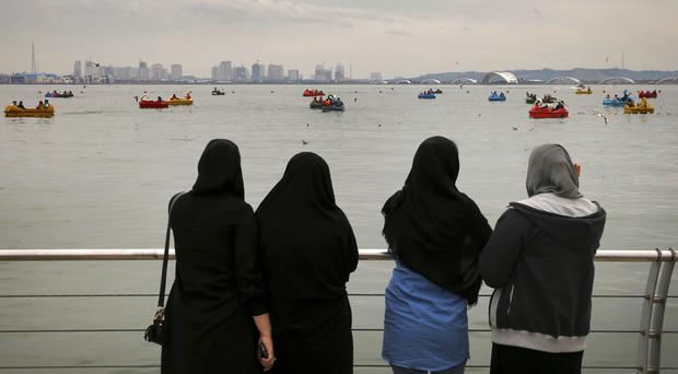For nearly 40 years, women in Iran have been forced to cover their hair and wear long, loose garments (Ebrahim Noroozi/AP)
