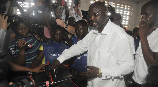 Former soccer star George Weah casts his vote during the presidential election in Liberia (AP/Abbas Dulleh)