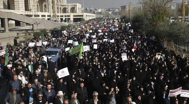 Iranian protesters chant slogans at a rally in Tehran (AP)