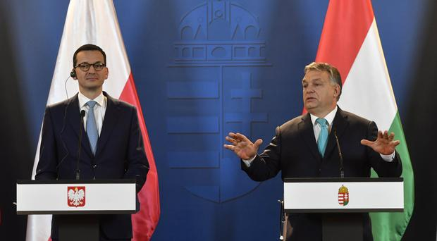 New Polish PM Mateusz Morawiecki, left, listens to his Hungarian counterpart Viktor Orban during their joint news conference following talks in the parliament building in Budapest (AP)