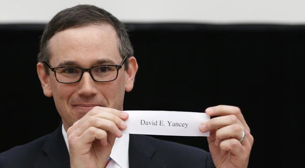 Virginia State Board of Elections chairman, James Alcorn, holds up the name of David Yancy, the winner of a drawing of lots to decide a House of Delegates seat (AP Photo/Steve Helber)