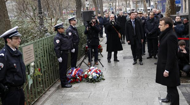French president Emmanuel Macron observes a minute of silence in front of the plaque commemorating late police officer Ahmed Merabet to mark the third anniversary of the attack, in Paris (AP)