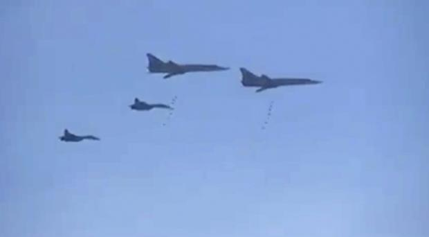 Russian bombers escorted by fighter jets bomb a target in Syria in a photo from footage from the Russian Defence Ministry official website (AP)