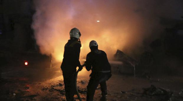 The Syrian Civil Defence White Helmets tackle a fire following a bombing that targeted the office of the militant group Ajnad al-Koukaz (AP)