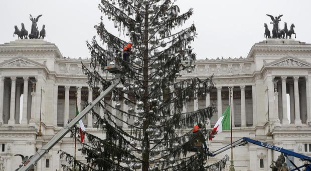 Workers dismantle Rome's official Christmas tree in front of the Unknown Soldier monument in the centre of the city (Riccardo Antimiani/ANSA via AP)