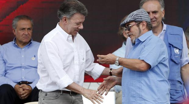 President Juan Manuel Santos shakes hands with Rodrigo Londono, Farc's top commander, last June, as peace talks with another rebel group hit problems (AP Photo/Fernando Vergara, File)