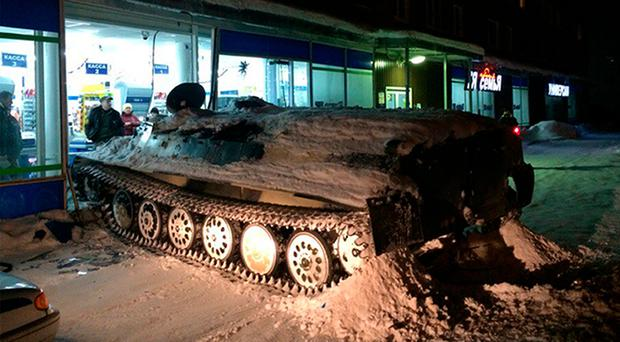 An armoured personnel carrier sits next to a shop window it crashed into in Apatity in the Murmansk region (Hibinform/Photo via AP)