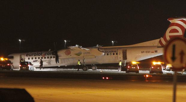 A Polish LOT airline passenger plane with its nose down on the runway after making an emergency landing with 59 passengers and four crew aboard at the international Chopin Airport in Warsaw, Poland (AP)