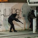 Riot policemen hide behind a wall during anti-government protests in Tunis (Amine Landoulsi/AP)
