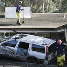 Emergency crew members search an area damaged by storms in Montecito, California (AP/Marcio Jose Sanchez)