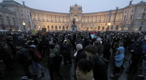 Protesters walk during a demonstration against the new Austrian government in front of the Hofburg palace in Vienna (Ronald Zak/AP)