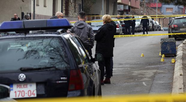 Police officers secure the scene where unknown assailants opened fire and killed Kosovo Serb politician Oliver Ivanovic (AP)