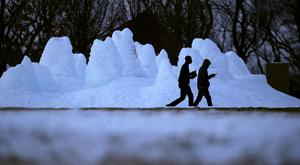 People walk past a frozen fountain at a park in Kansas City, Missouri (AP)