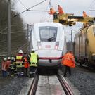 Rescue workers try to remove a tree from an ICE train of Deutsche Bahn stands on the rail track near Lamspringe between Hannover and Goettinge (AP)