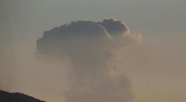 A plume of smoke rises on the air from inside Syria, as seen from the outskirts of the border town of Kilis, Turkey (Lefteris Pitarakis/AP)
