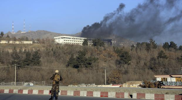 An Afghan security official stands guard near the Intercontinental Hotel in Kabul