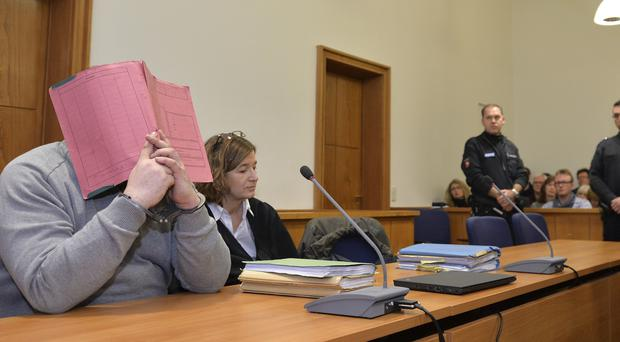 Niels Hoegel covering his face at a 2015 court appearance (Carmen Jasperson/AP)