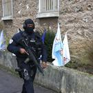 A hooded police officer patrols outside the Fresnes prison (AP)